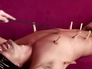 Blondfolded dude with pegs on his body receives spanking